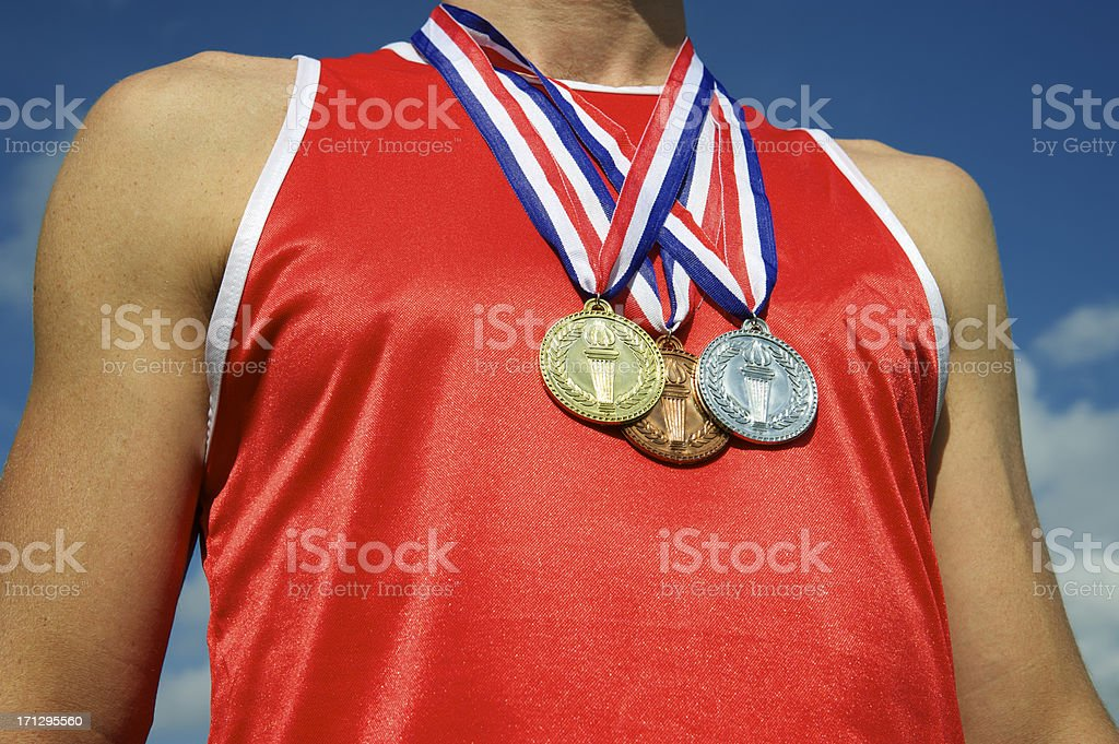 Athlete with Gold Silver Bronze Medals Bright Blue Sky stock photo