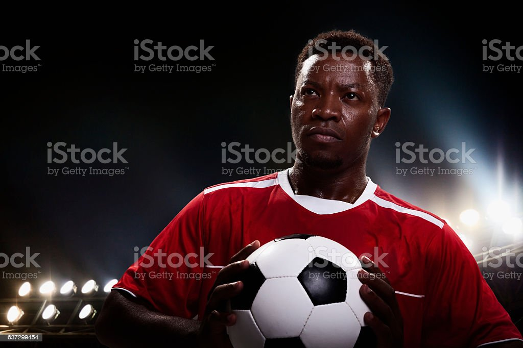 Athlete with soccer ball in stadium arena looking forward stock photo