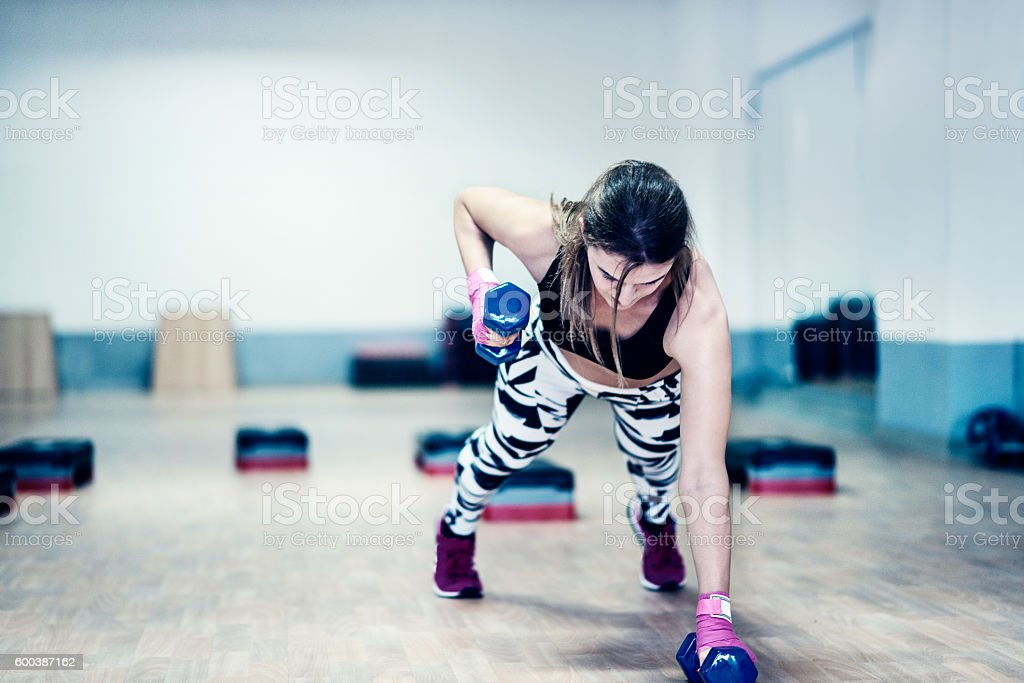 Athlete Woman Doing Push-ups and Lifting Weights in Gym stock photo