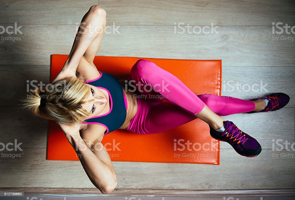 Athlete woman doing sit ups for abdominal muscles on mat stock photo