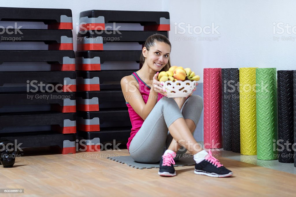 Athlete Woman Holding Fruit Basket on a Break in Gym. stock photo