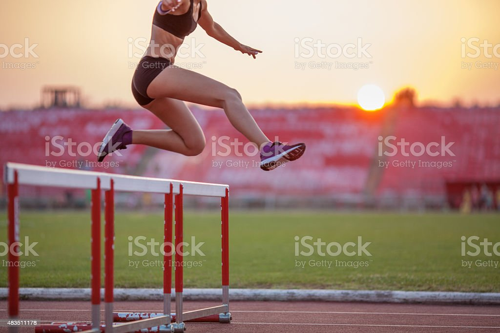 Athlete woman hurdling stock photo