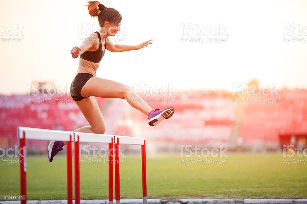 Athlete woman hurdling stock photo