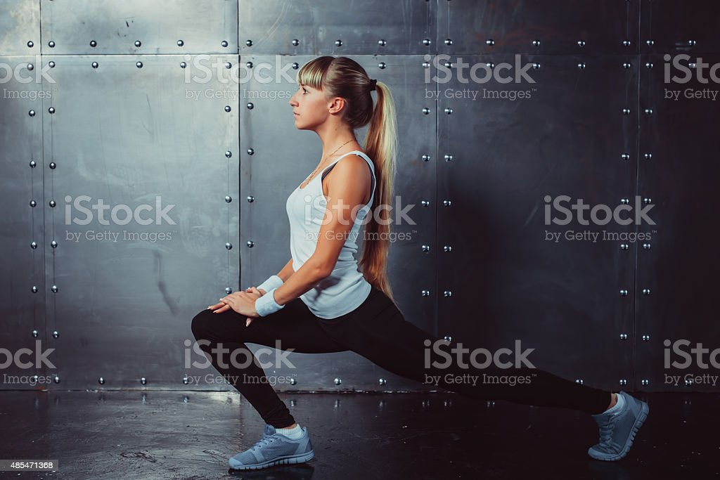 Athlete woman stretching legs in gym doing fitness exercise concept stock photo