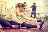 Athlete young woman stretching legs
