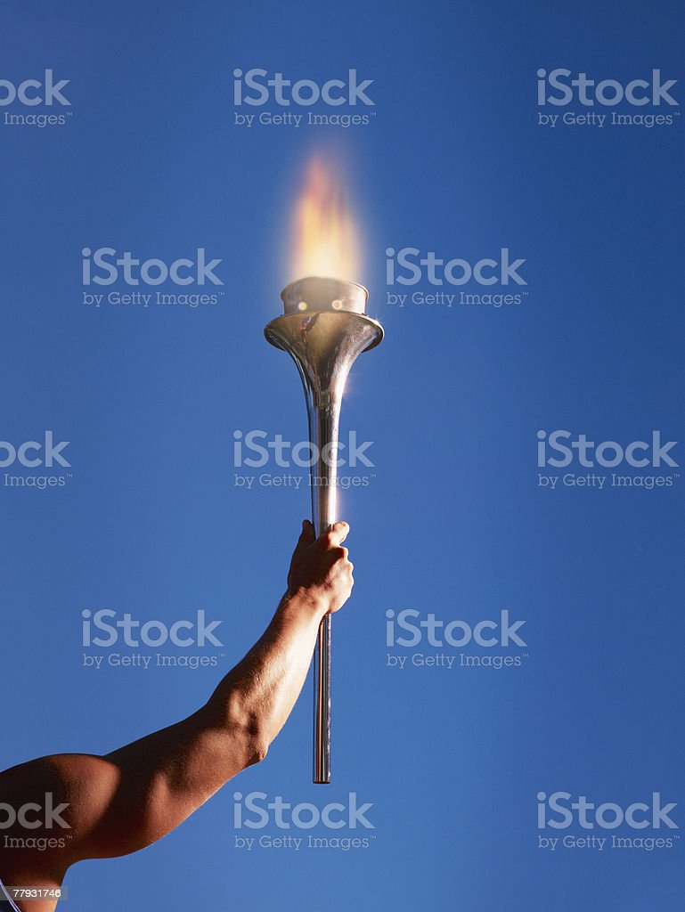 Athlete's arm holding up a torch stock photo