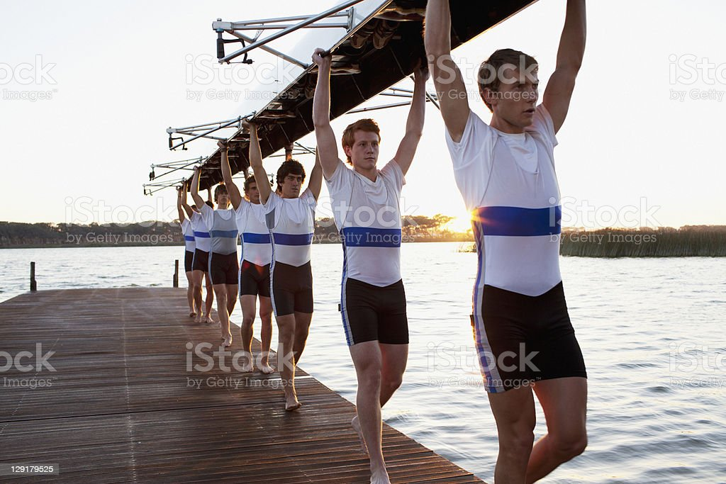 Athletes carrying a crew canoe over heads stock photo