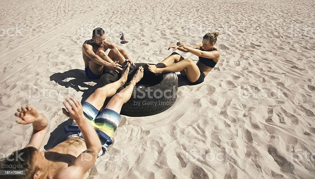 Athletes doing sit-ups on tire royalty-free stock photo