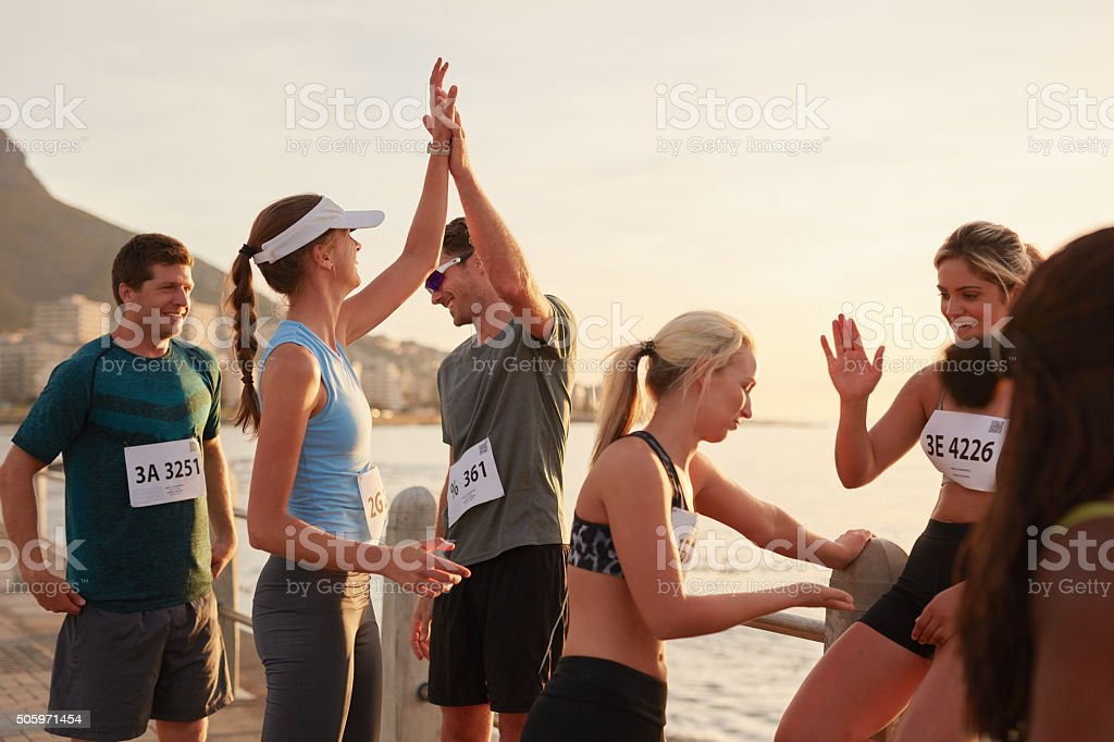 Athletes high fiving after a race stock photo