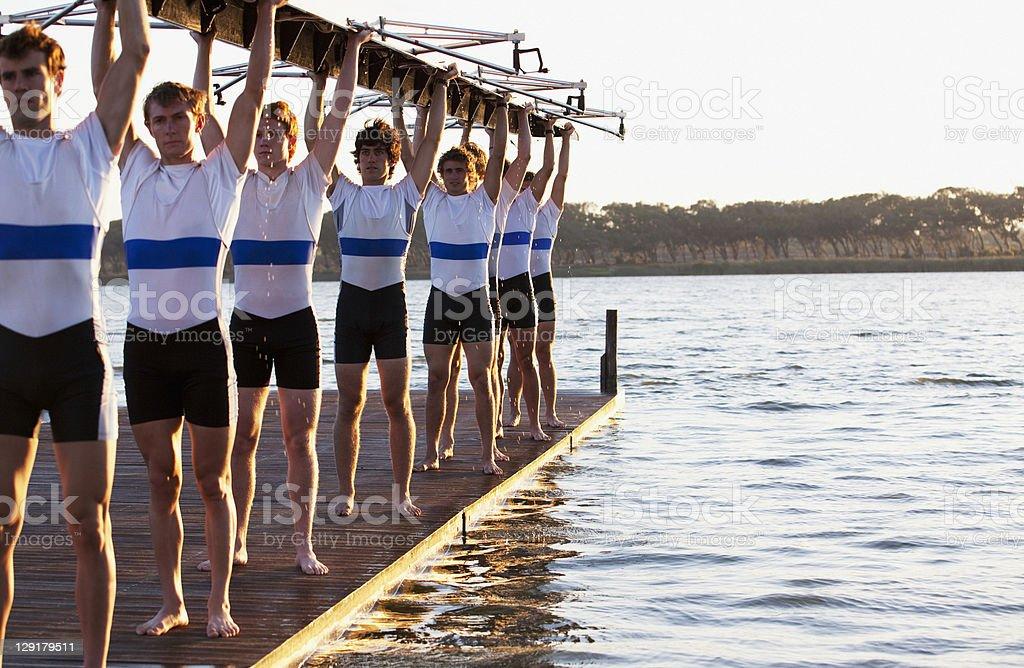 Athletes holding a crew canoe over heads stock photo