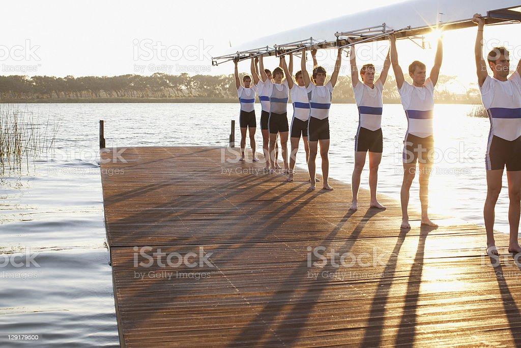 Athletes holding their boat upwards stock photo