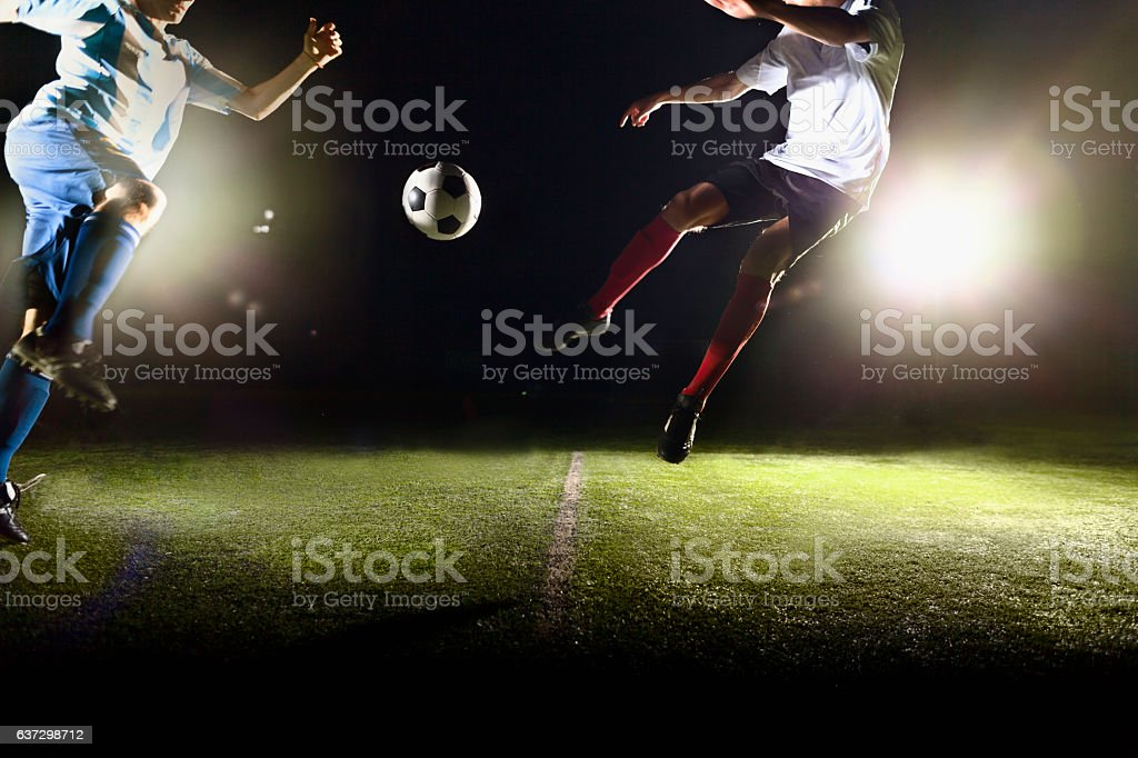 Athletes jumping towards soccer ball on field during game stock photo