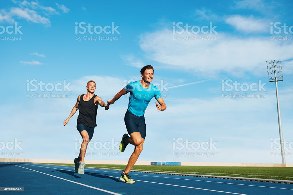 Athletes pass the baton in a track relay stock photo