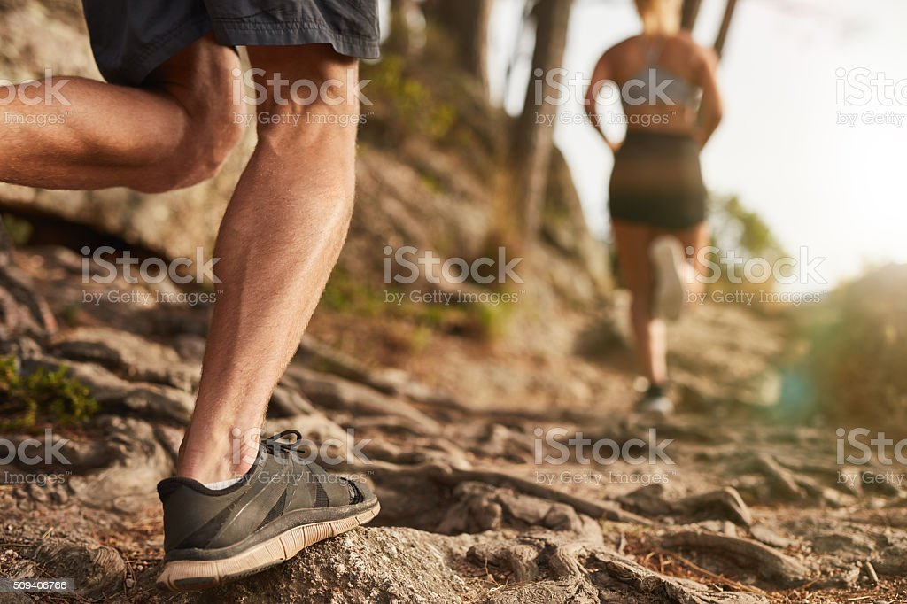 Athletes run through rocky terrain stock photo