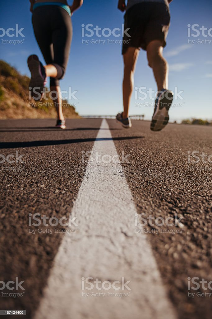 Athletes running on country road stock photo