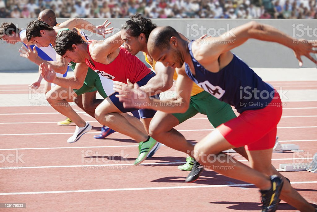 Athletes running on sports track royalty-free stock photo