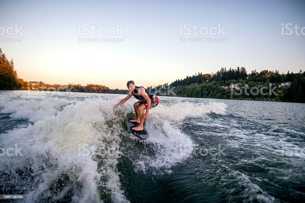 Athletic adult male wake surfing stock photo