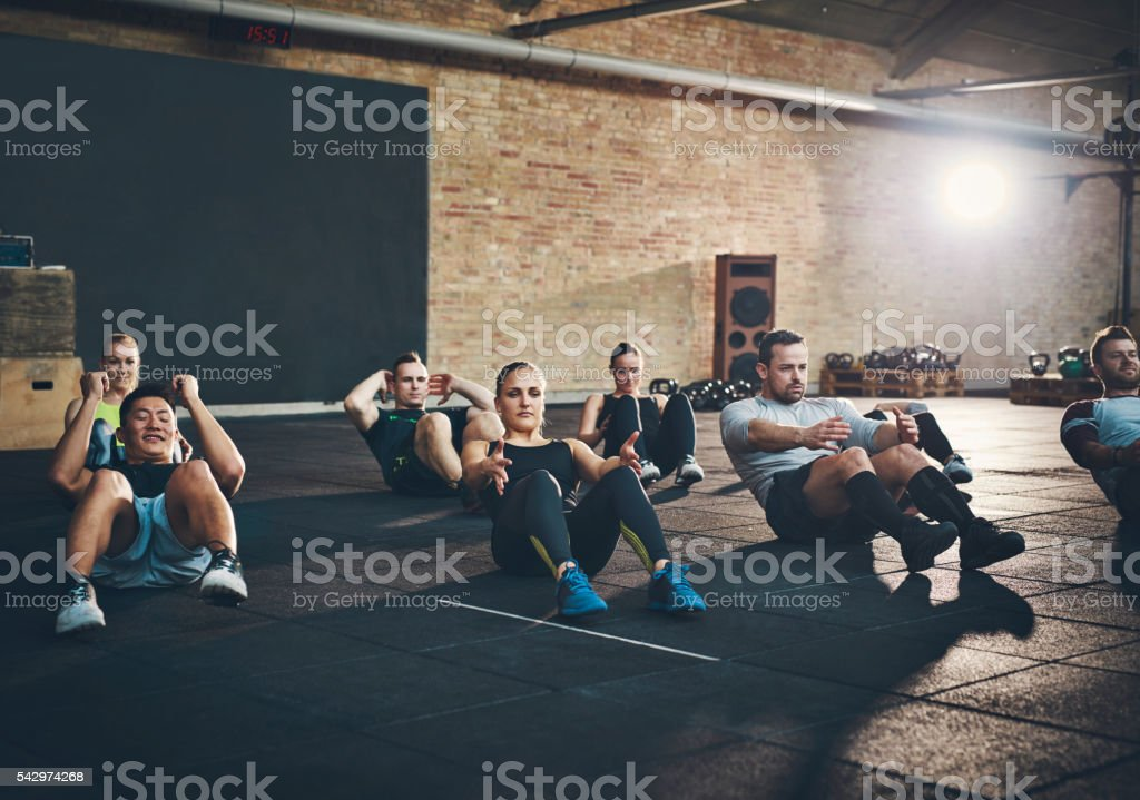 Athletic adults performing sit up exercises stock photo