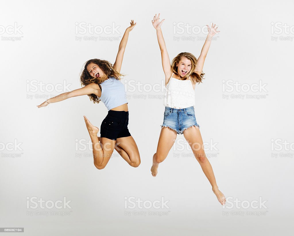 Athletic and energetic young beauties jump into the air, laughing stock photo