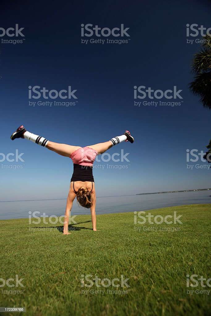 Athletic and Flexible woman doing a Cartwheel Handstand on Grass royalty-free stock photo
