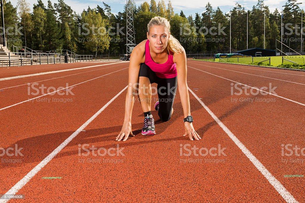 Athletic beautiful female runner in start position on running track stock photo
