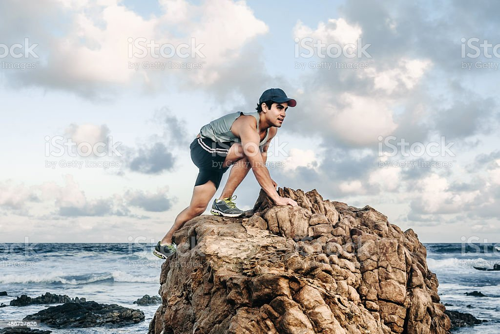 athletic beautiful sportsman climbing cliff in ocean at brazilian coast stock photo
