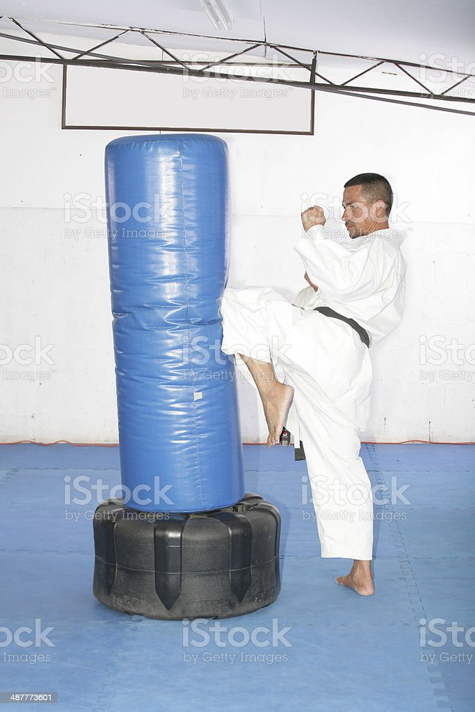 Athletic black belt karate giving a forceful knee kick stock photo