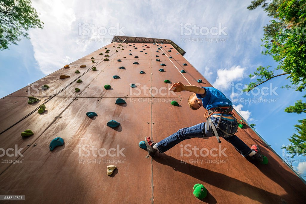 Athletic boy is training on outdoor artificial climbing tower wall stock photo