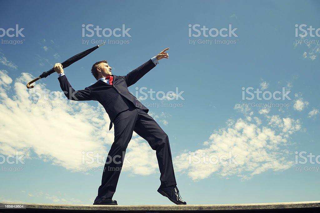 Athletic Businessman Standing Outdoors Throwing Javelin Umbrella Blue Sky stock photo