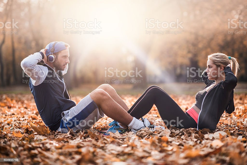 Athletic couple cooperating while doing sit-ups on autumn leaves. stock photo