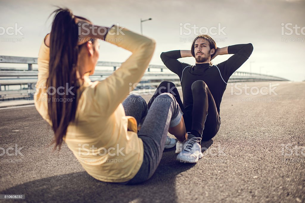Athletic couple doing sit-ups on a road. stock photo