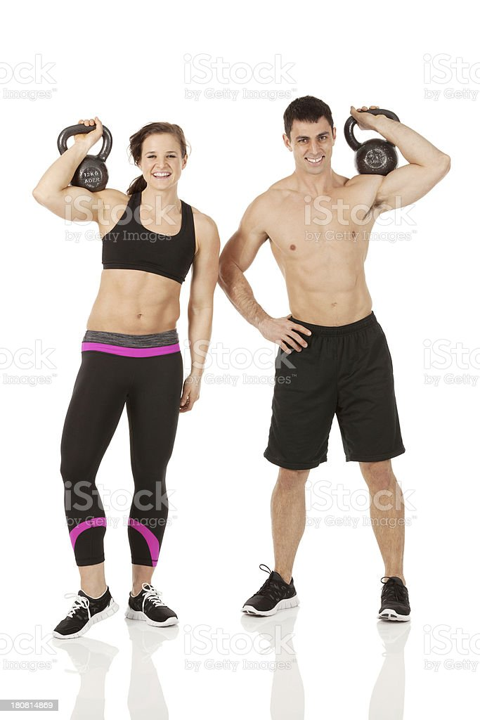 Athletic couple standing with kettlebells royalty-free stock photo