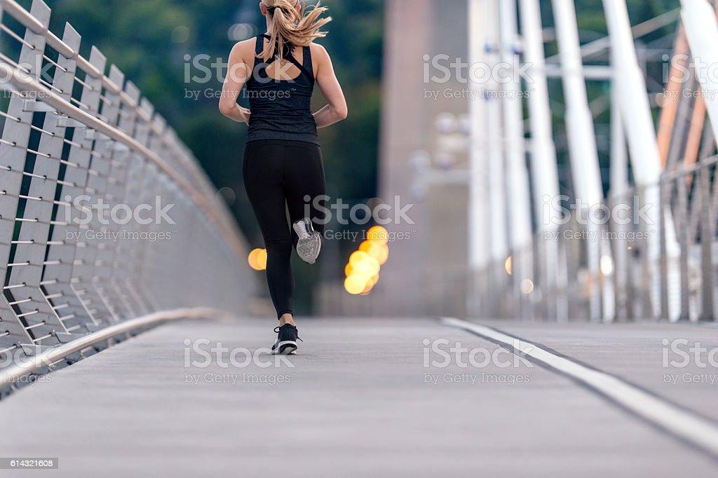 Athletic female figure sprinting across a bridge stock photo