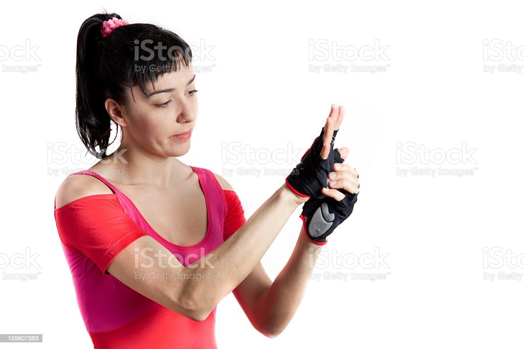 Athletic female puts on the gloves for gym exercises stock photo