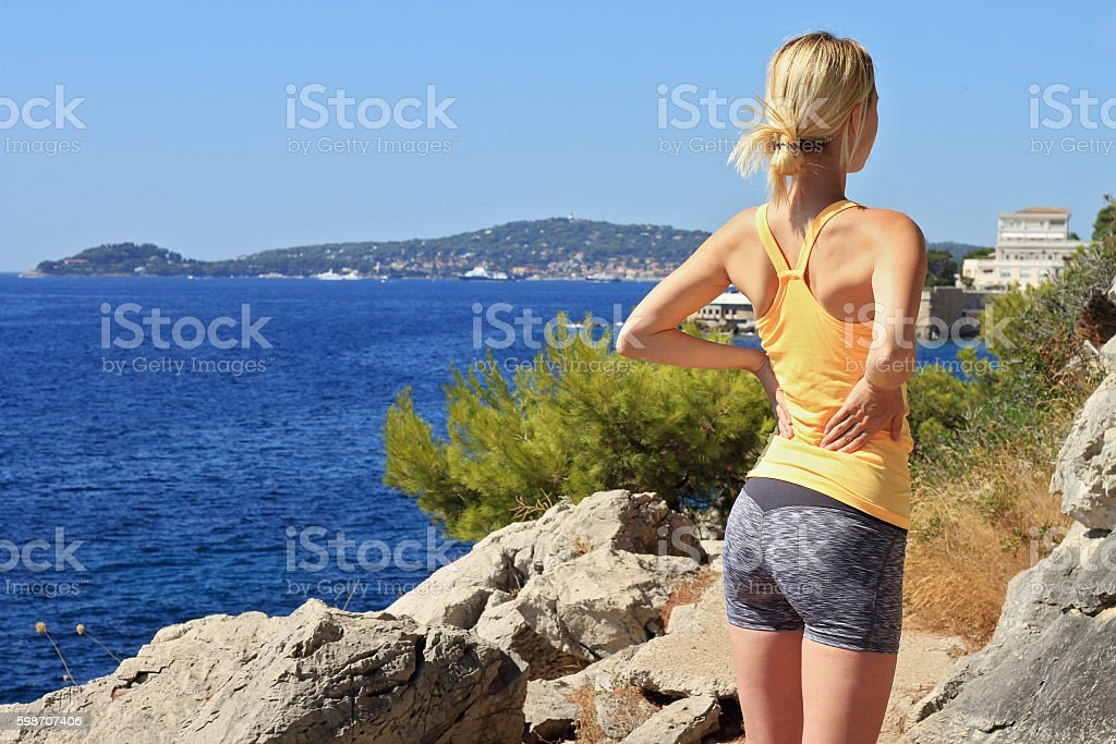Athletic fitness woman rubbing the muscles of her lower back stock photo