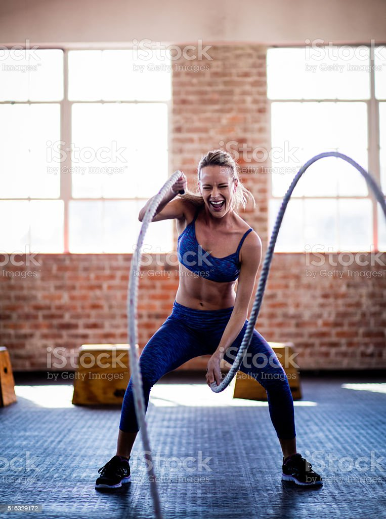 Athletic girl efforting on gym training with ropes at gym stock photo