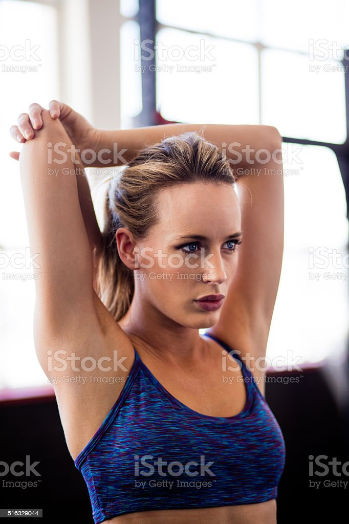 Athletic girl warming up before gym workout at gym stock photo
