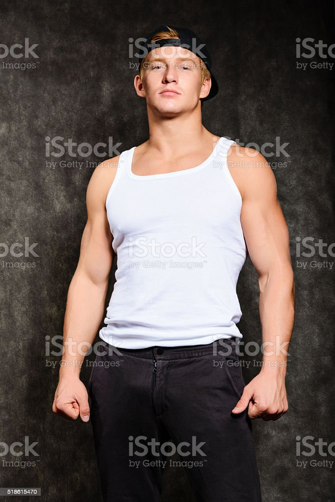 athletic guy in a vest and  baseball cap stock photo