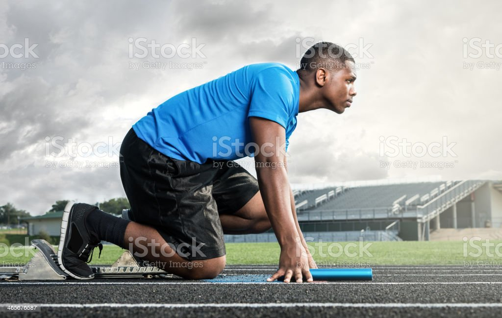 Athletic High School Track Star on Starting Block Before Race stock photo