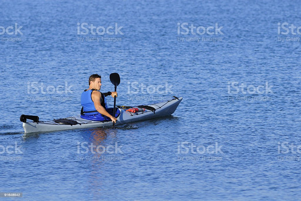Athletic kayaker rows off royalty-free stock photo
