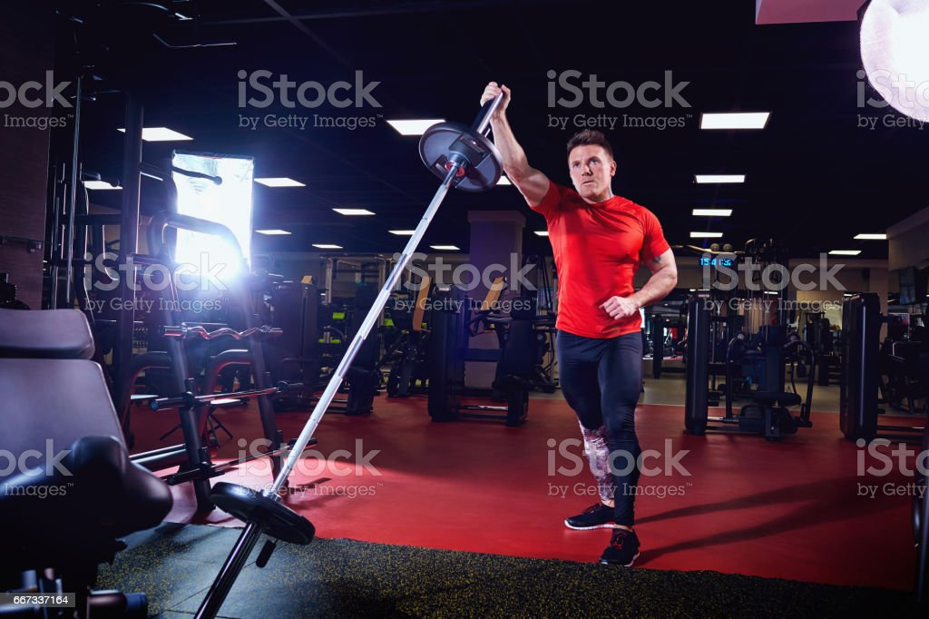 Athletic male athlete doing exercises with a barbell in the gym stock photo