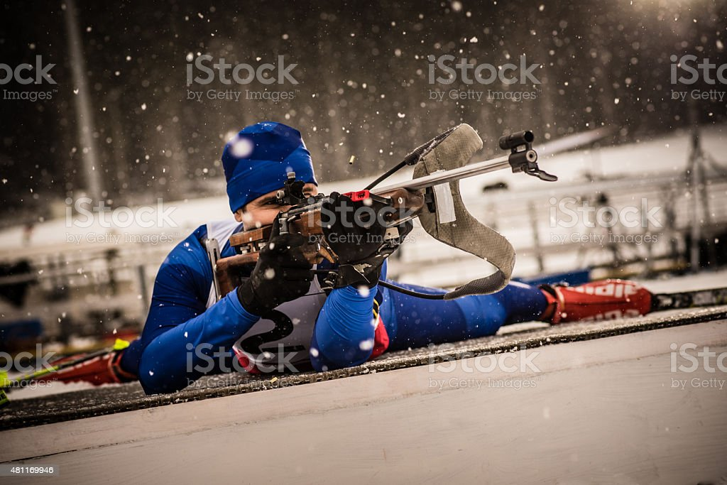 Athletic man aiming with biathlon rifle stock photo