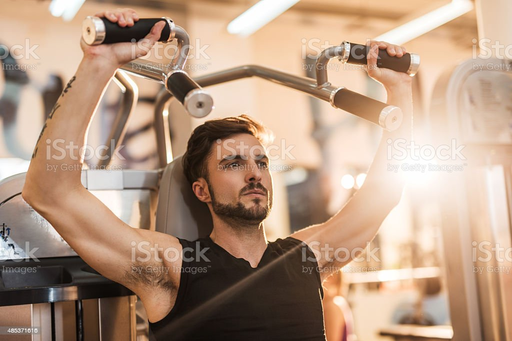 Athletic man doing body building exercises in a health club. stock photo