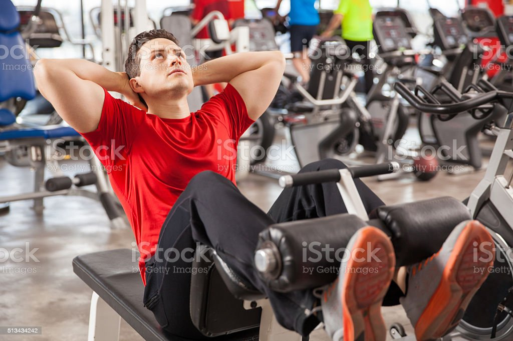 Athletic man doing crunches in a gym stock photo