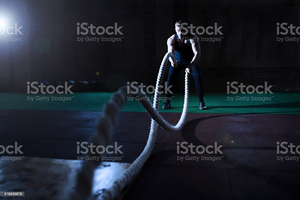 Athletic man doing crossfit exercises with a rope in gym stock photo
