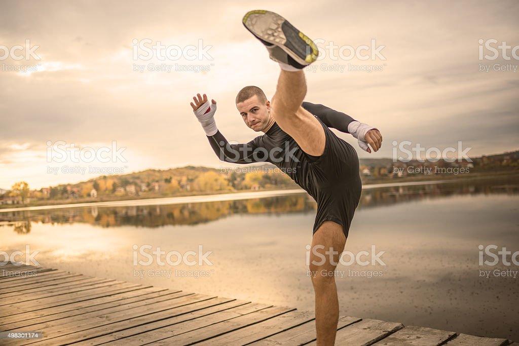 Athletic man doing  kick outdoors stock photo