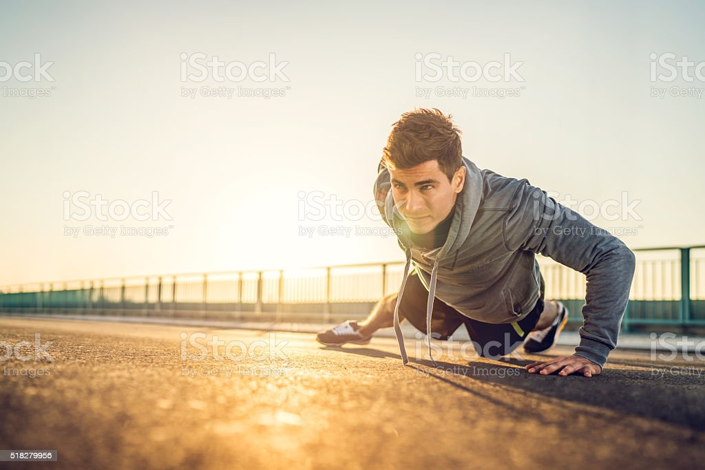 Athletic man doing push-up on a road at sunset. stock photo