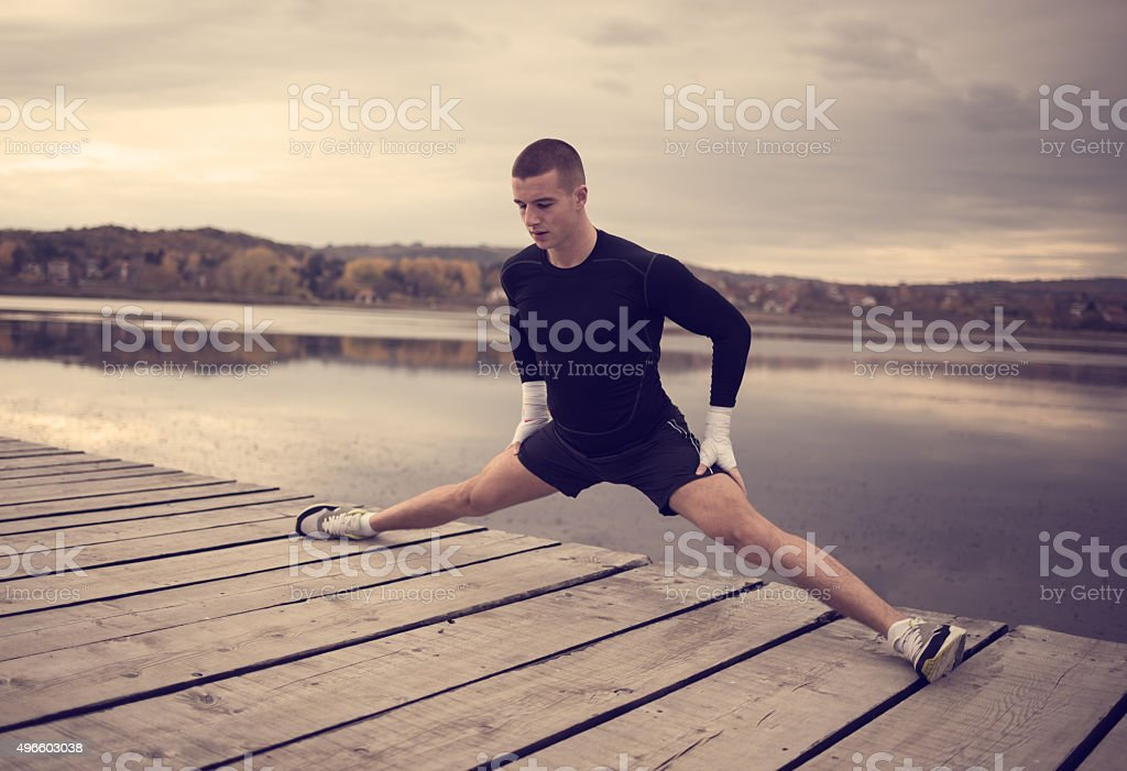 Athletic man doing stretching exercises outdoors stock photo