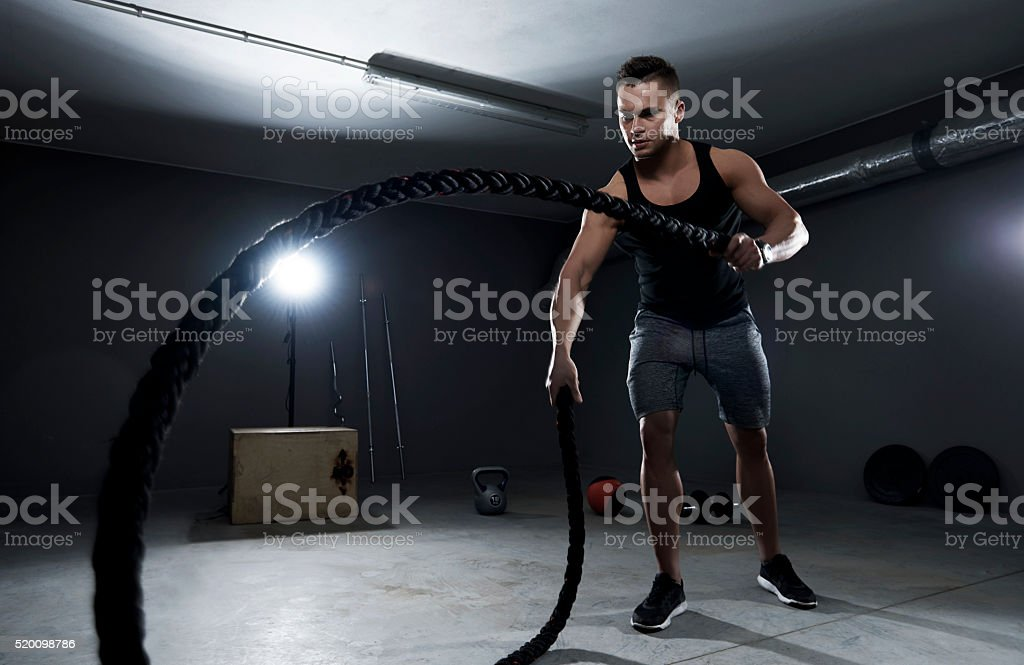 Athletic man efforting on training with ropes stock photo