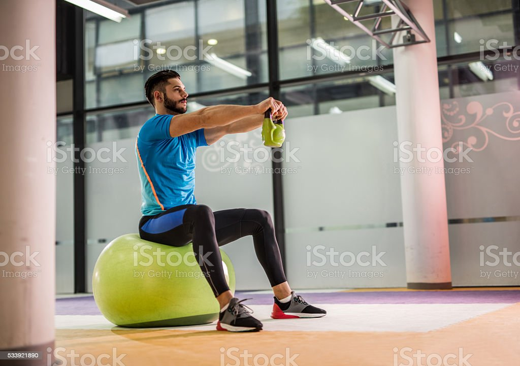 Athletic man exercising with kettle bell in a gym. stock photo